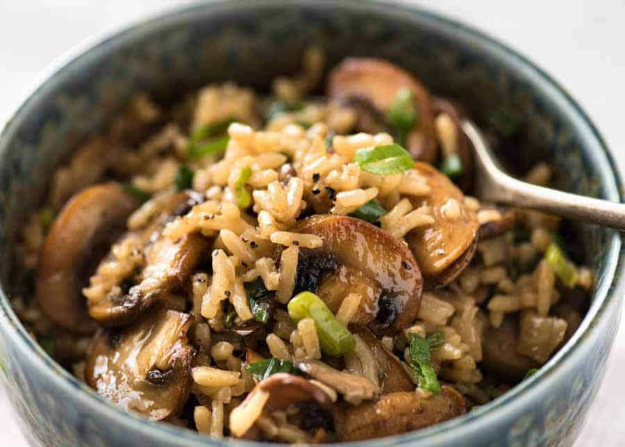Mushroom Rice in a rustic blue bowl with a fork, ready to be eaten
